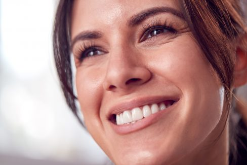 Close Up Portrait Of Relaxed And Natural Looking Woman Smiling At Home