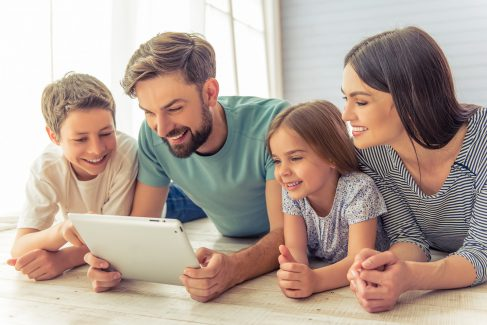 Beautiful young parents, their cute little daughter and son are using a tablet and smiling, lying on the floor at home